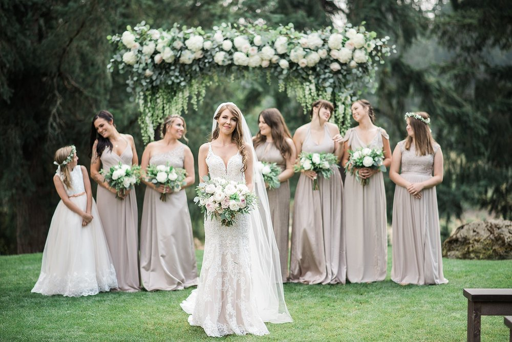 The bride & her bridesmaids in front a gorgeous white & green fl