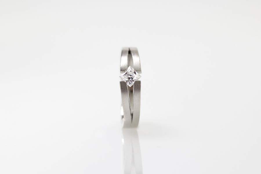 Anel de noivado Claris, em ouro branco 18k e diamante quadrado (lapidação princesa).