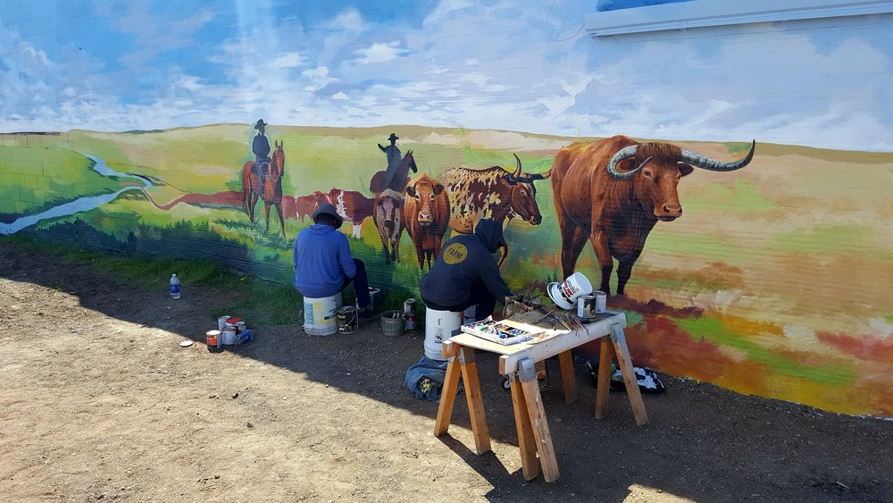 A mural in Boss Cowman Square in progress. This hand painted mural will be the back drop for the sculpture that I am doing for the square.