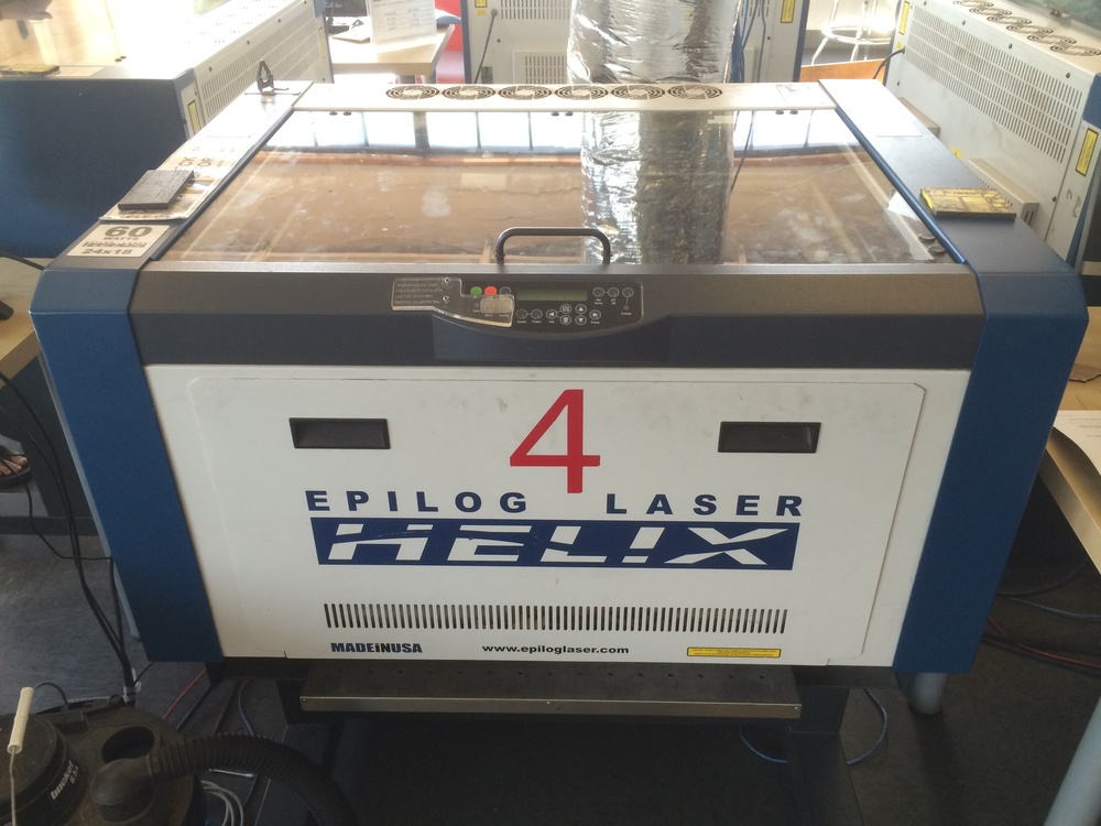Epilog Helix 24 Laser Cutter Uses lasers to cut and engrave flat or round surfaces. Specs: - Laser area 610 x 457mm - Max material thickness 216mm - Resolution is user controlled from 75 to 1200dpi - Up to 60 Watts of power - Cuts wood, plastics, leather, and etc, but not metal or glass - Engraves almost any material