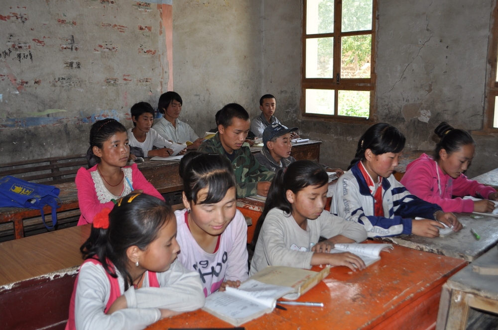 Students from Rugan Nang Village sharing textbooks to study Tibetan language.