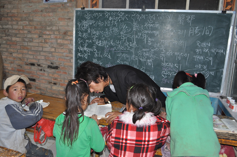 Pade Gyal, a volunteer teacher, uses a combination of Chinese and Tibetan language to explain aspects of Tibetan culture to the students.