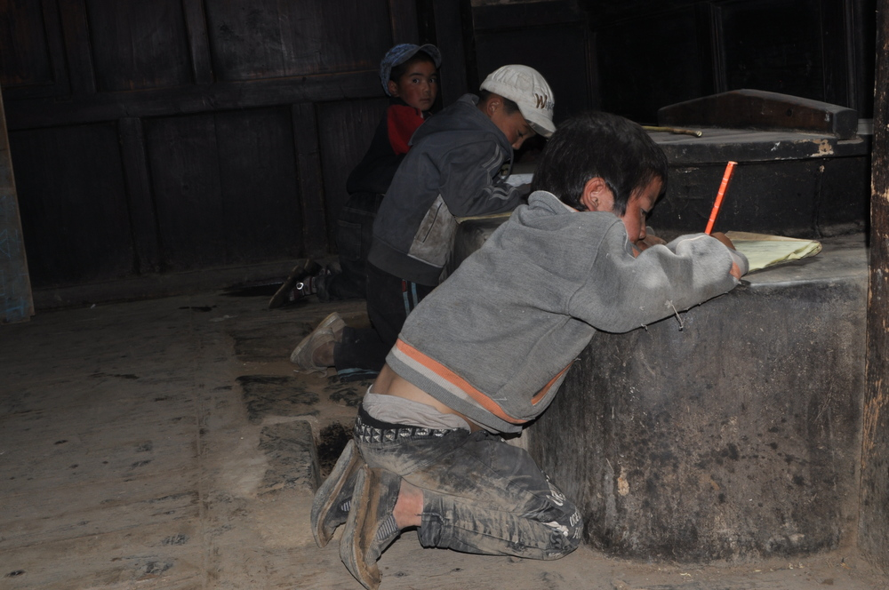 Students using the kitchen stove in the village temple as a desk to practice writing the Tibetan alphabet.