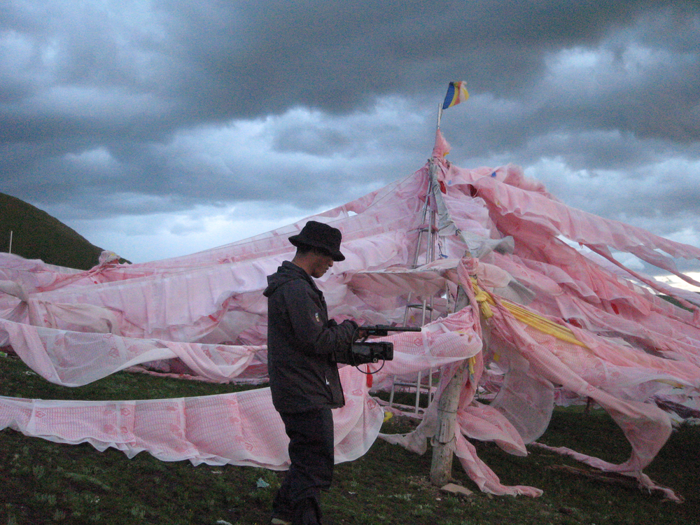 Tsering Perlo filming prayer flags near Sershül Monastery