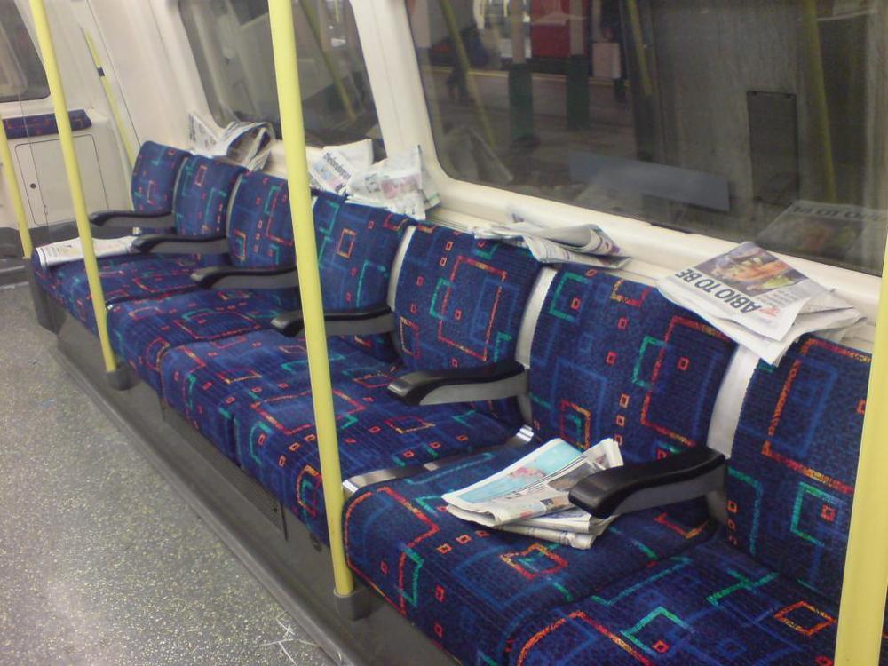 Free_newspapers_on_london_tube_train.jpg