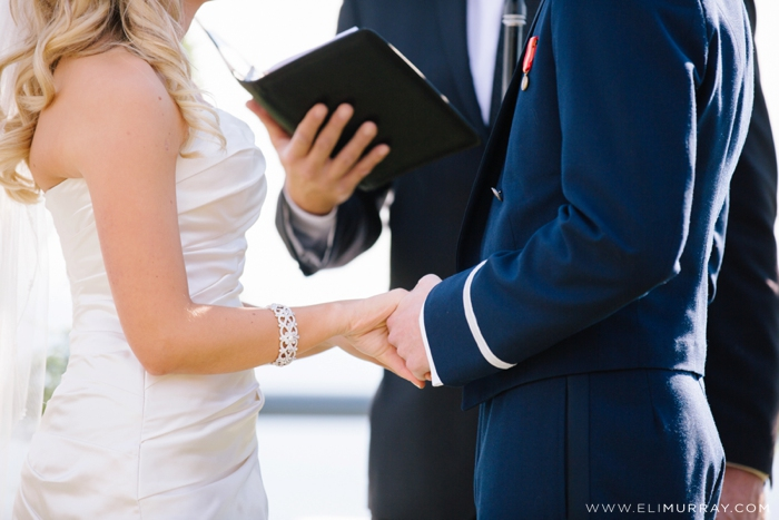 bride and groom hold hands in ceremony