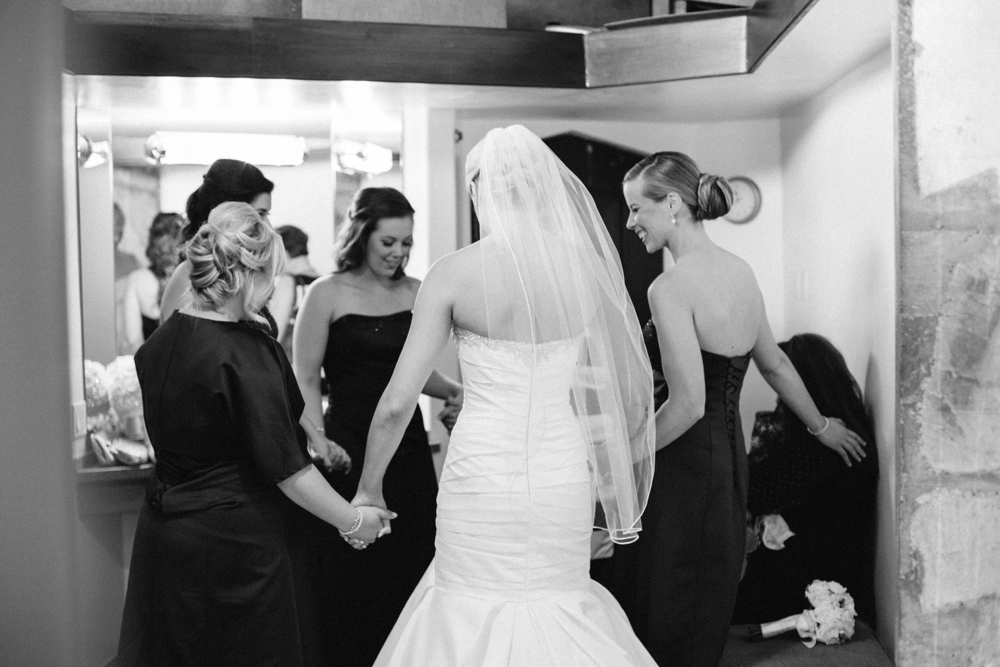 bride and bridesmaids praying together