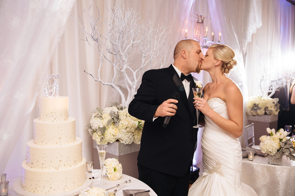 Bride and groom kissing in behind cake
