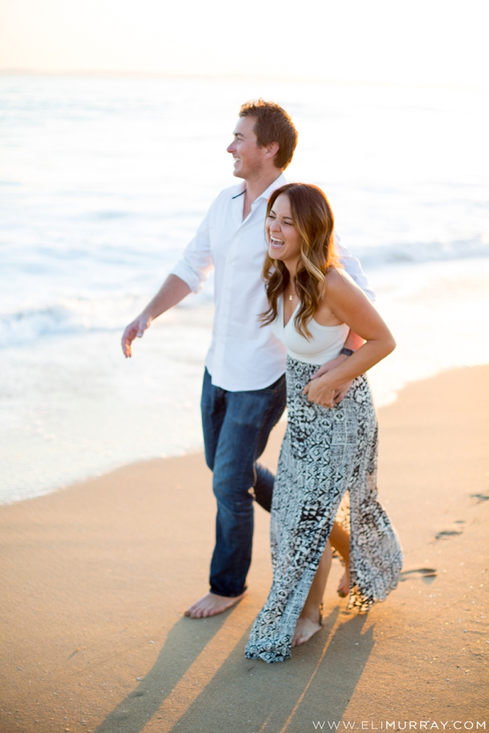 Engaged couple laughing on the beach