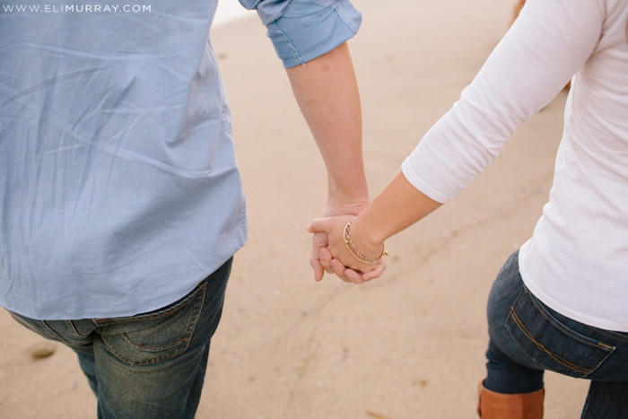 Couple holding hands while they walk in Laguna Beach