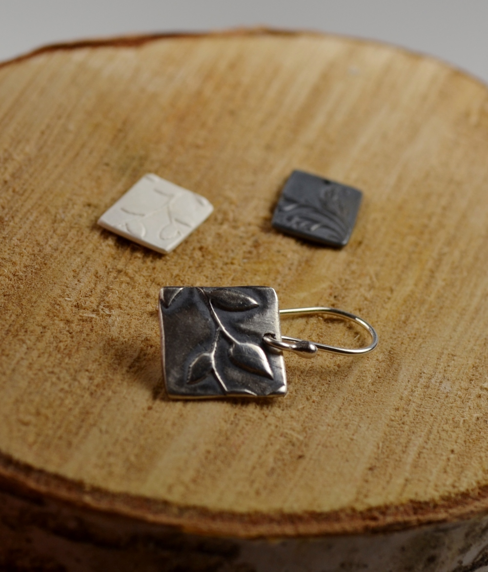 Three pieces of fine silver.  From left: white just out of the kiln, black after oxidizing, polished and finished as an earring.