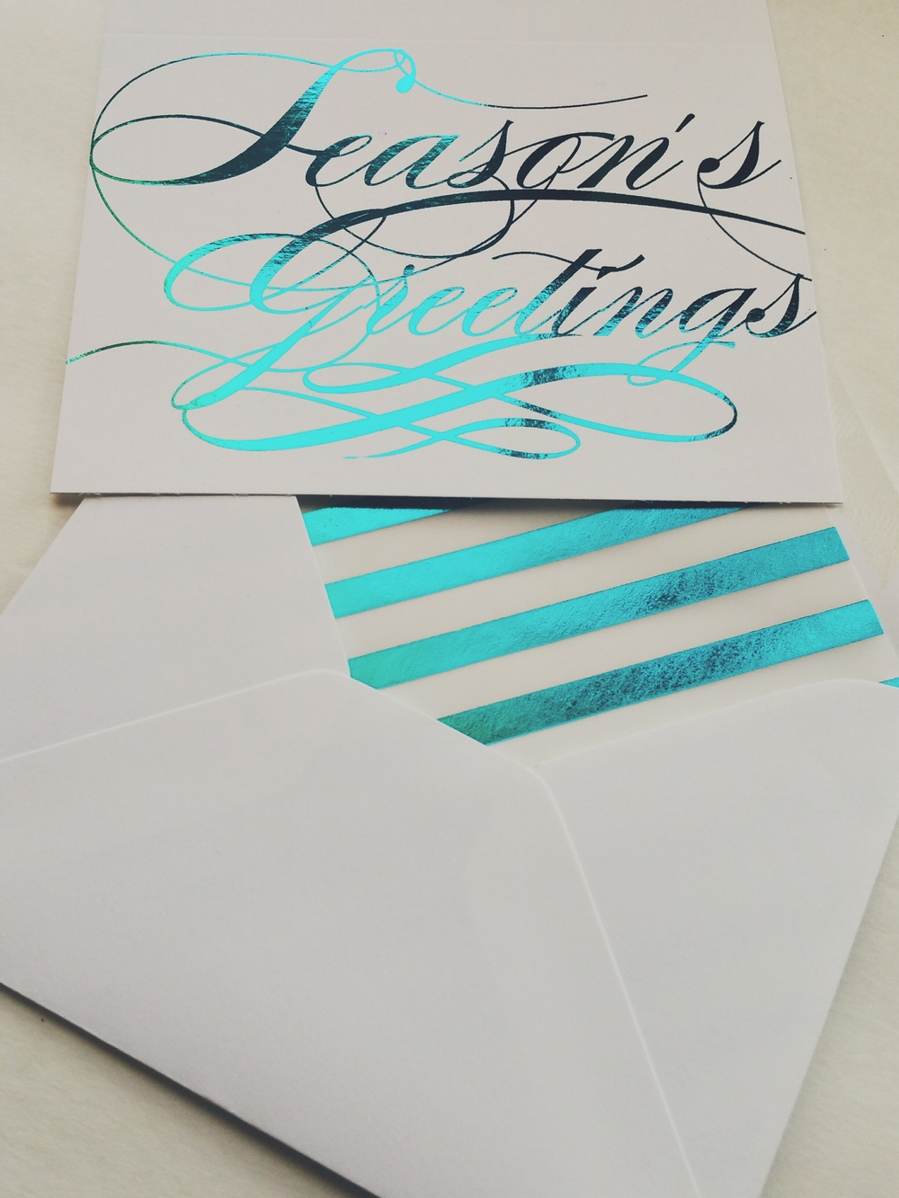 Teal Foil Season's Greetings Holiday Card with custom striped teal liner.