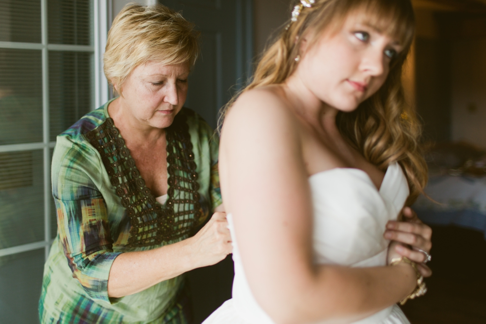 Bride getting into her Watters Wedding Dress at the Gettysburg Battlefield B&B in Gettysburg PA, Hair by Downstreet Salon, Makeup by Texture Salon, Wedding Photographers With Love & Embers
