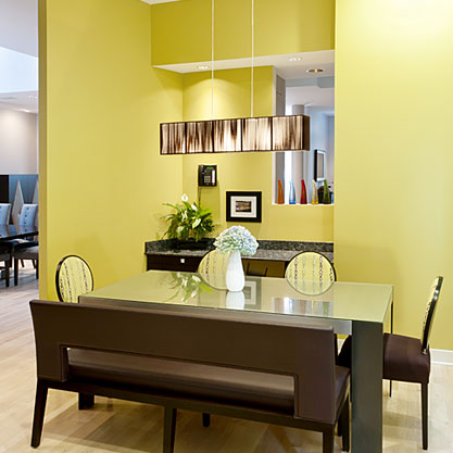A kitchen nook that previously housed a banquette was redesigned and enlarged to incorporate a work space and new eating area. Existing windows were removed and larger ones installed to add more light. A large pendant light hangs over a custom made metal table creating an intimate, fun and functional area for the family to enjoy. A bright citron color present on the walls and accented in the upholstery adds energy to the space.