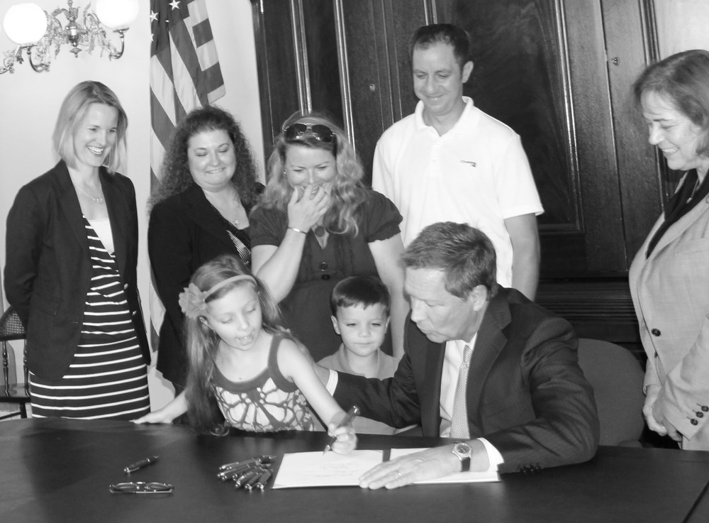 Governor John Kasich, Ohio watching as siblings of Sophia Capo sign SB4 into legislation.