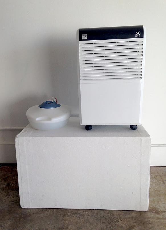 Respirateur , humidifier, dehumidifier, 2014  A humidifier and a dehumidifier sit beside one another on a pedestal, one adding humidity while the other subtracts. Neither one makes any progress in adjusting the climate of the room.