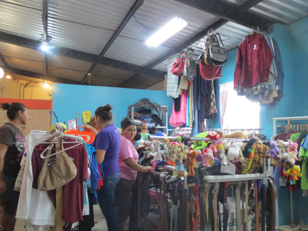 Salvadoran women selecting gently used clothes they will sell as part of the SonRia entrepreneurship program.