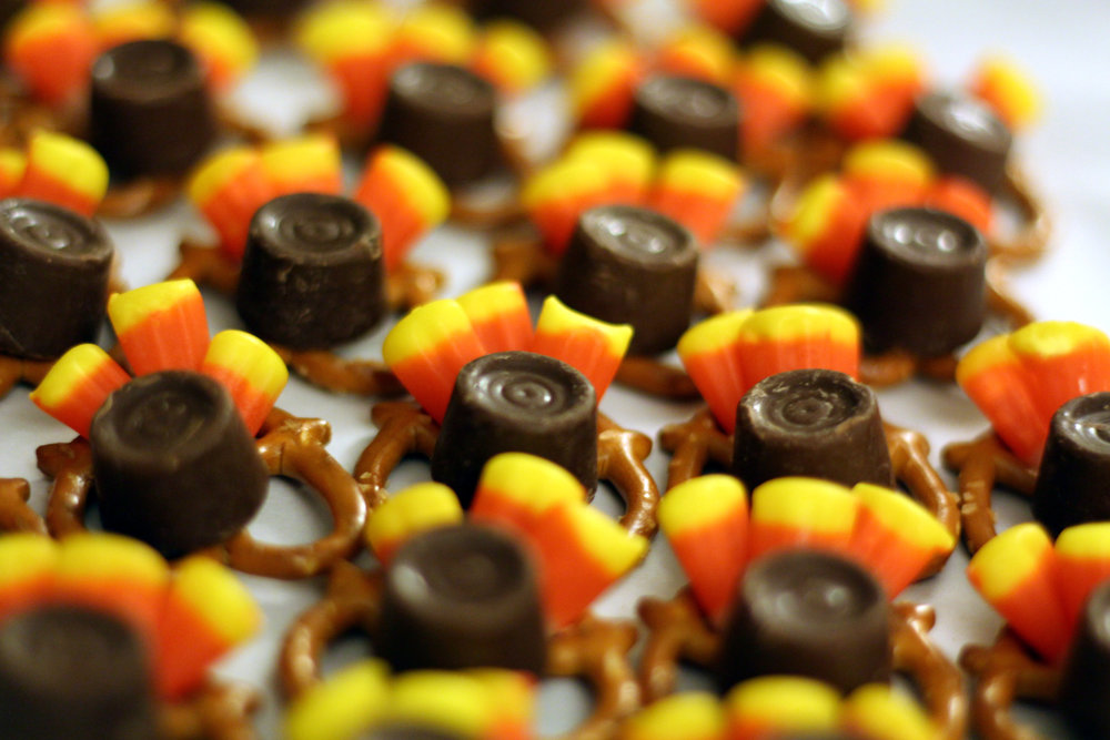 Start by placing three candy corn in the main weave of the pretzel then balance a Rolo in the center. Put in the oven (300 degrees F) for 5-6 minutes to melt the candy together.