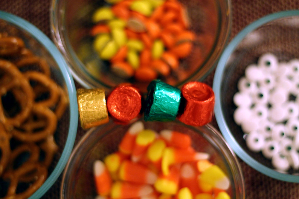 Ingredients Needed? Rolo Chocolates, Pretzels, Candy Corn, Reese's Pieces (I cut them in half using a pill slicer) and Candy Eyes. Mommy Octopus called for White Candies and to get the eyes you would dip a toothpick in the melted chocolate and dot on. I just so happened to stumble across candy eyes at Target!