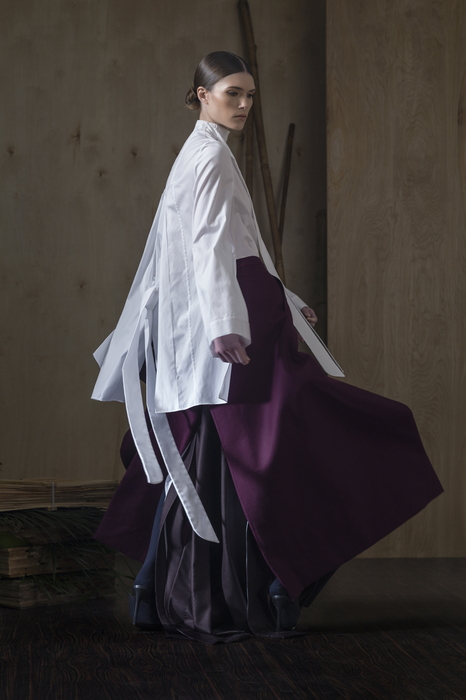 Oxford Cotton L/SLV Blouse with Tie and Seam Extrusion Details  Paired With  Plum Overlap Skirt and Deep Plum Super Overlap Trousers. Polished, Stoned Brooch.
