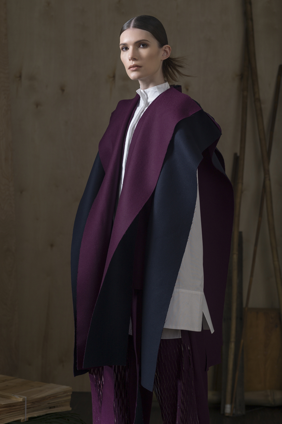 Oxford Cotton L/SLV Blouse with Exposed Back, Side Slits and Seam Extrusion Details  Paired With  Plum Slitted Trousers and Staggered Wool Paneled Over-Vest.