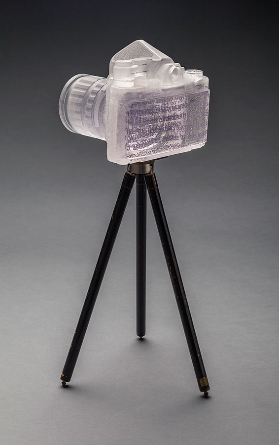 Ptolemy's Pentax  (back view); 2014; 7 x 7.5 x 6 inches; cast glass, ceramic decal, paint, antique Kodak tripod