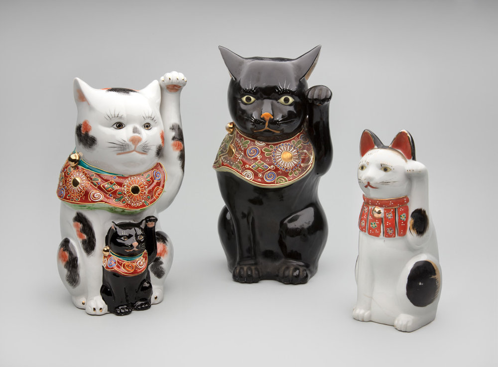 Left to right:  Kutani kilns, Japan. Maneki neko with kitten 20th century, porcelain. Gift of Billie L. Moffitt. Mingei International Museum 2010-04-044 L2017.3201.011  Kutani kilns, Japan. Maneki neko 20th century, porcelain. Gift of Billie L. Moffitt. Mingei International Museum 2010-04-115 L2017.3201.026  Seto kilns, Japan. Maneki neko 20th century, porcelain. Gift of Billie L. Moffitt. Mingei International Museum 2010-04-029 L2017.3201.046