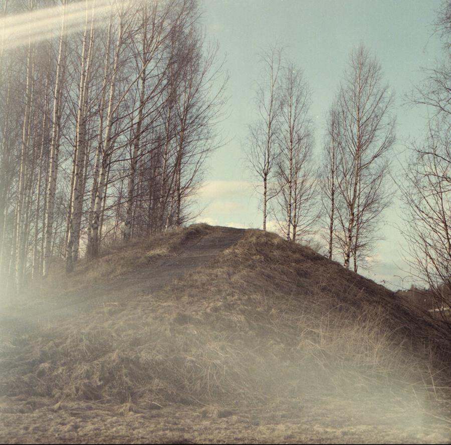 """Kuva  sarjasta Kaukovainio , 2017. Kuvattu filmille.   """"Elä nyt Kaukovainiolle, se on ihan hullu paikka, Villin lännen paikka.""""   Kukaan ei synny tyhjään maailmaan eikä jätä tyhjyyttä jälkeensä. Asuinpaikat, toiset ihmiset, yhteisöt jättävät meihin jälkensä ja me niihin. Valokuvausprojektini päähenkilö on murrosvaiheessa oleva metsälähiö Kaukovainio. Se on matalan tulotason ja korkeiden työttömyyslukujen lähiö Oulussa. Kaukovainion kaltaisia, 1960- ja 70-luvulla rakennettuja huonomaineisia lähiöitä löytyy jokaisesta suomalaisesta kaupungista. Pelkkä kaupunginosan nimi on monelle paikalliselle synonyymi vuokrataloille, sosiaalisille ongelmille ja päihteille. Lähiö on koti kuitenkin yli neljäsosalle suomalaisista. Paikka johon kaivataan. Suomessa 1960- ja 1970-lukujen valtava massamuutto maalta kaupunkiin johti lähiöiden syntymiseen. Minua kiinnostaa - itsekin 70-luvun pellolle rakennetulta asuinalueelta kotoisin olevana - miten paikasta, johon kenelläkään ei ollut juuria, syntyi juureva kotiseutu.  Kaukovainio on kiehtova paikka ristiriitaisuudessaan: se on yhtäaikaa tavallinen ja absurdi, maaseutumainen ja urbaani, lähiö metsässä. Lähiössä kohtaavat yksinäisyys ja yhteisöllisyys, se voi olla väliaikainen kämppä elämän muutosten keskellä tai koti jo perheen neljälle sukupolvelle. Kaukovainio on myös omaleimaisen pohjoinen lähiö: kotipihalta pääsee hiihtämään, ostarilta voi ostaa puolukat, kodeissa puhutaan rehevää Oulun murretta.  Kaukovainio-projektista on suunnitteilla kirja, yhdessä tutkija, kasvatustieteen tohtori  Uma Louhelan kanssa. Hän on kerännyt Kaukovainiolla asukkaiden tarinoita ja muistoja, jotka liittyvät ihmisten arkeen, elämään, kokemuksiin asuinpaikastaan. Kirjahanketta tukee Pohjois-Pohjanmaan kulttuurirahasto.   Kaukovainio - lähiötarinoita -sarjan aikaisemmat muotokuvat  yhdessä Uma Louhelan keräämien tarinoiden kanssa ovat olleet esillä mm. Oulun taidemuseossa."""