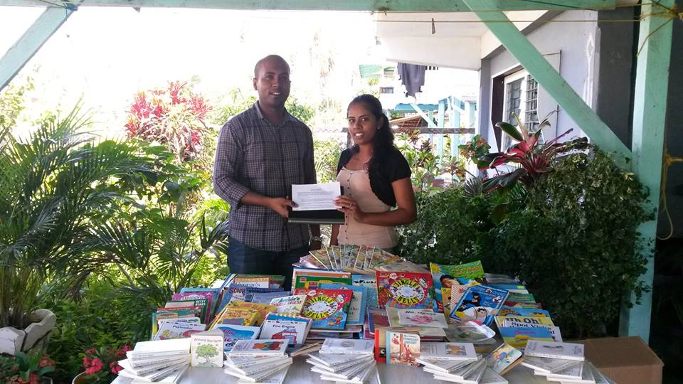 President of Youths in Unison, Rebekah Timram, receiving children's storybooks from GF's Managing Director, Mr. Anthony Autar.