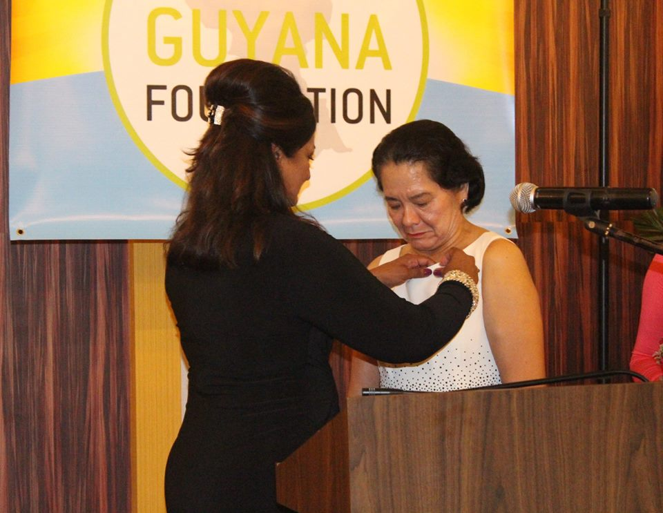 First Lady, Mrs. Sandra Granger being presented with a gold pin by Founder of the Guyana Foundation, Mrs. Supriya Singh-Bodden