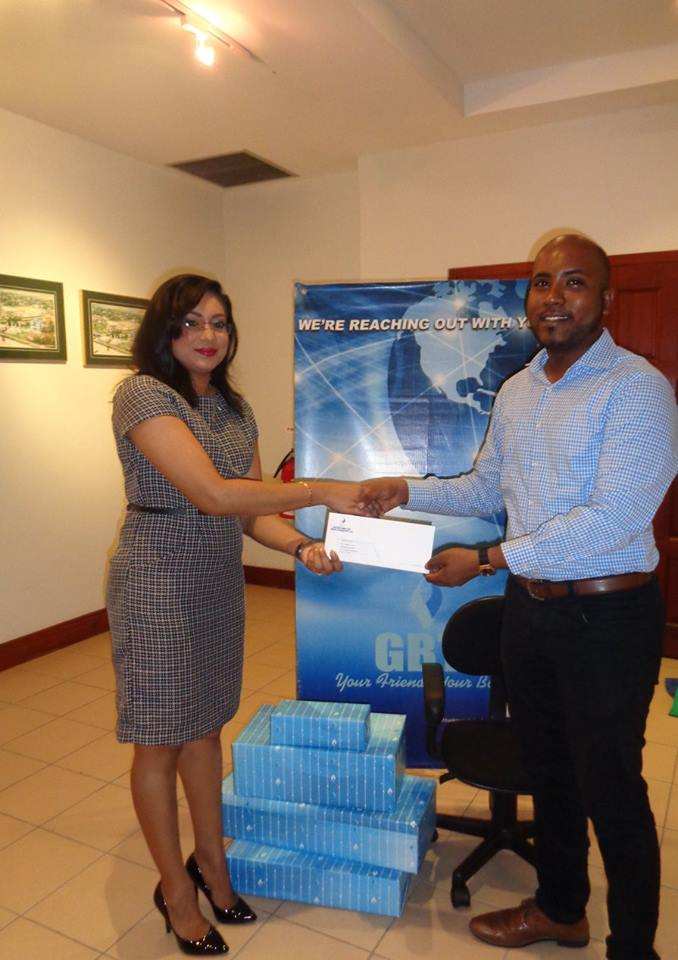 Managing Director of Guyana Foundation, Anthony Autar, receiving the donated items from Ms. Pamela Binda, Public Relations and Marketing Manager at GBTI