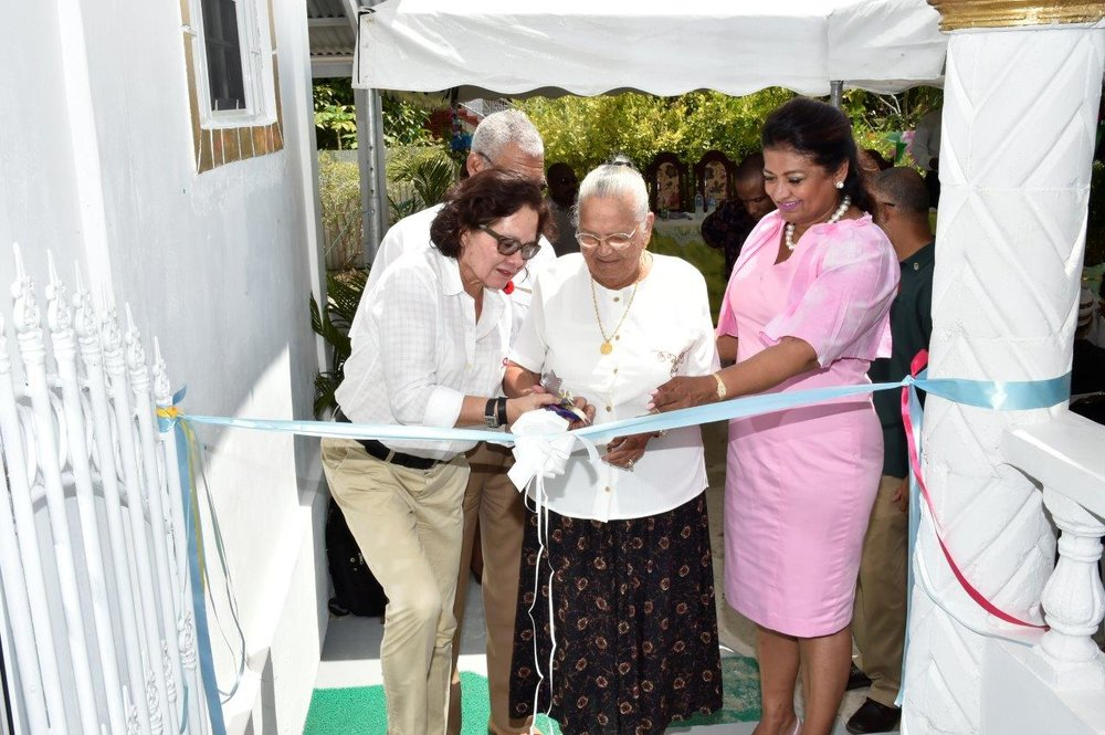 First Lady, Mrs. Sandra Granger and Mrs. Supriya Singh-Bodden help Mrs. Seraji Sankar to cut the ribbon to officially open the Guyana Foundation Sunrise Centre at Zorg-En-Vlygt, Essequibo Coast.