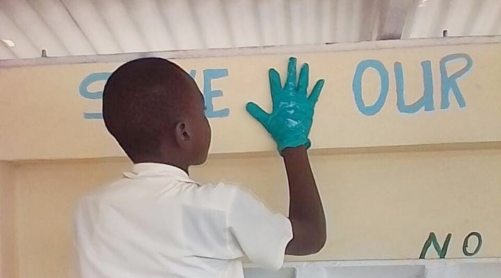 A school child doing a hand print on the wall of this school building as part of his message in the the effort to protect children from sexual abuse.