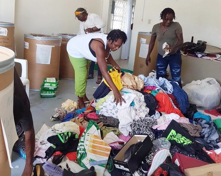 Volunteers helping to sort out clothing and other items from the barrels donated by Ms, Francis Yvonne Jackson.