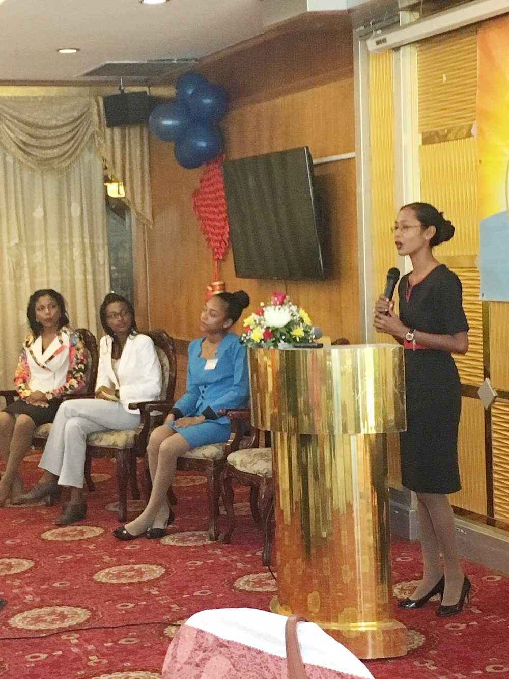 Candacie Calistro sharing her experiences. Sitting from left are the Child Crae Manager of the Sunrise Center, Madonna Paul, Nateefa John and Zohise Harris.
