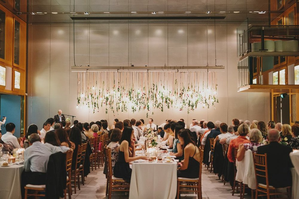 When a library is no longer a library. Main Event couple Irvin + Matt allowed us to get truly creative and transform what was a blank, concrete room in a Brisbane library into a wedding reception that goes in the record books. 1000's of hanging florals replaced the traditional fairy-lit bridal party table backdrop, framing the stars of the night beautifully. Photo via  Lover of Mine .