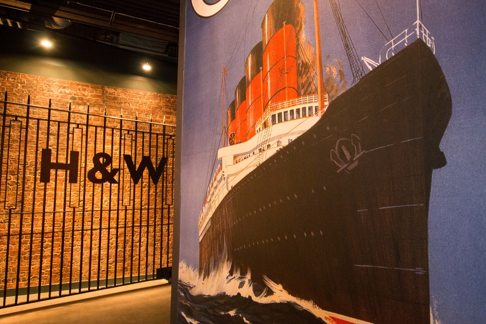 A mural of the Titanic with the actual gates from the Harland and Wolff shipyard from the Titanic era in the background.