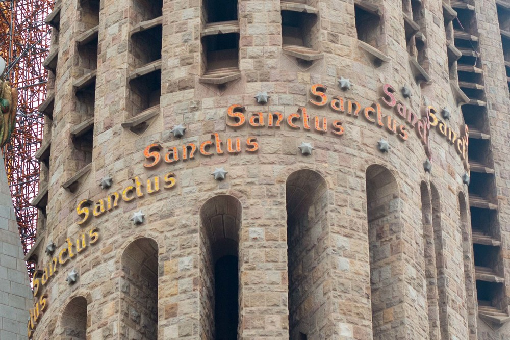 SANCTUS, LATIN FOR HOLY, INSCRIBED AROUND THE TOWERS ON THE PASSION FACADE