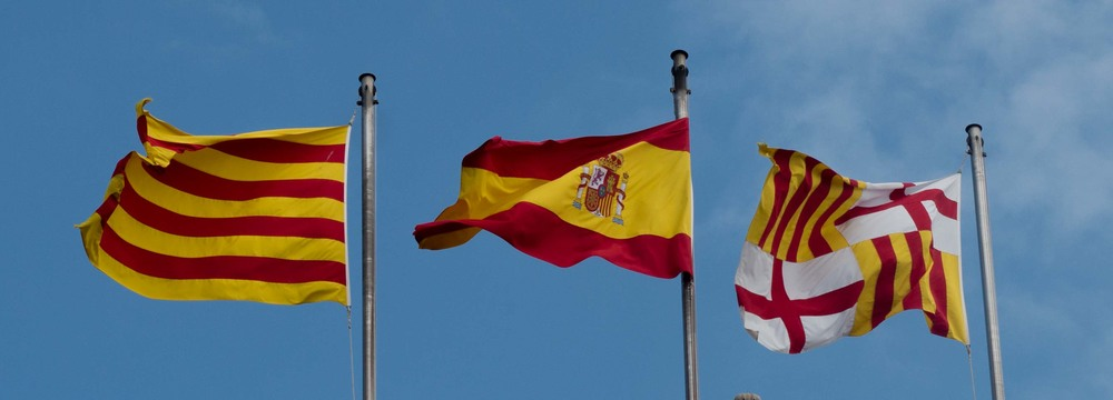 The Spanish flag flanked by the Catalan flag on the left, and the Barcelona Flag on the right
