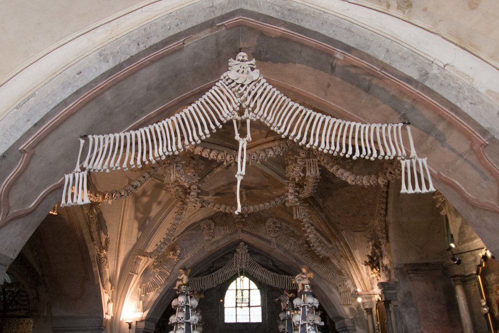 A garland of long bones hangs above the entrance