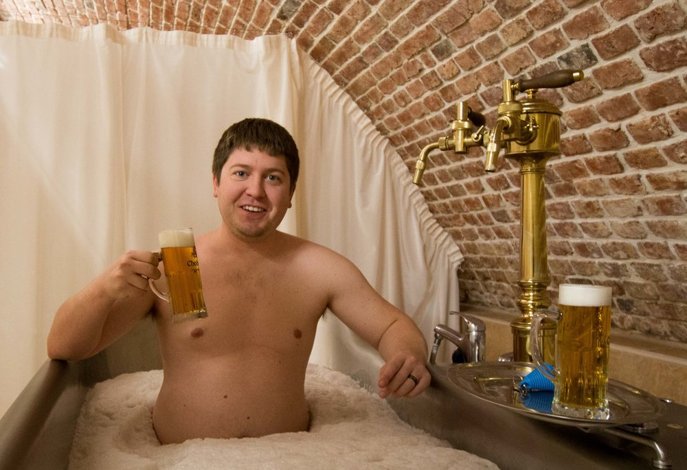 aaron drinking a beer while bathing in beer