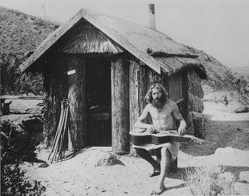 Bill Pester at this palm log cabin in Palm Canyon, California, 1917.