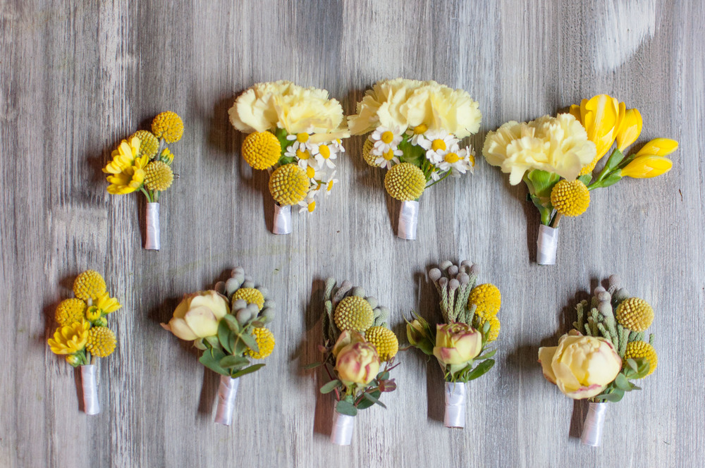Different boutonnieres in yellow, white and grey.