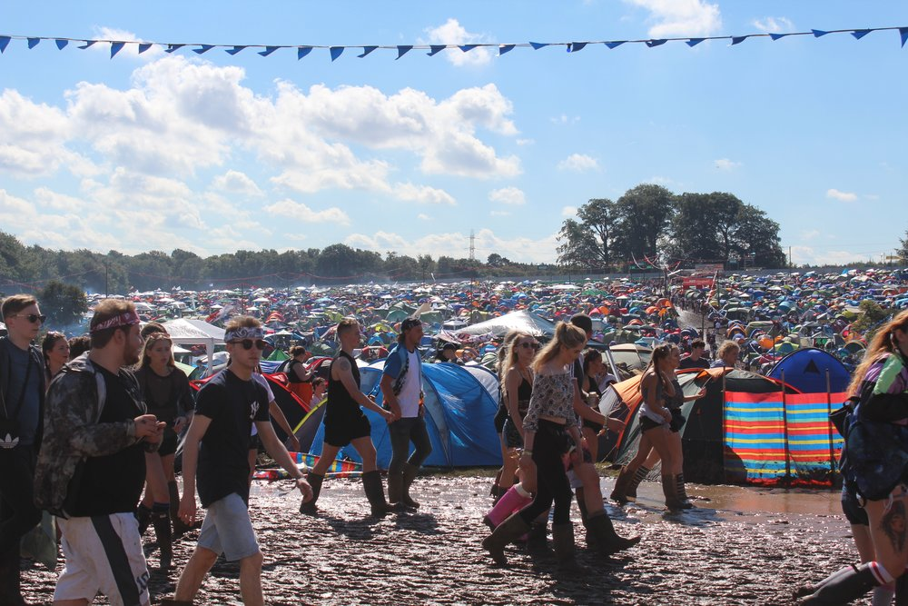 Festival goers brave the mud on a sunny Friday as temperatures reached 26C in the Sun, a little respite from the torrential rain Image Credit - (Sean Brown)
