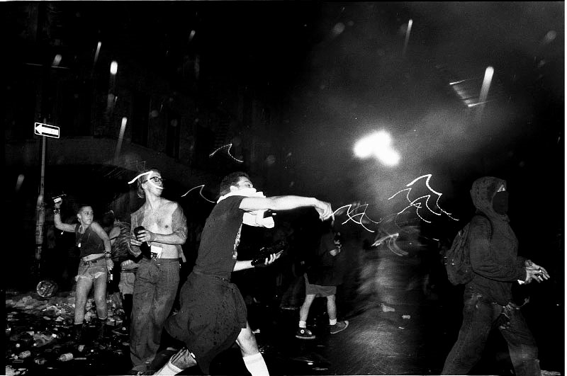 In Avenue A, in front of the Tompkins Square Park, anti-gentrification protesters hurl bottles at the riot-geared police forces. New York, May 27, 1991. -Q. Sakamaki