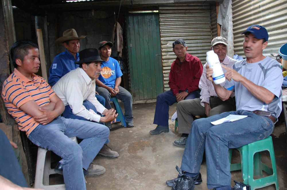 Timoteo teaching farmers in Santa Maria de Jesus about how to manage roya.