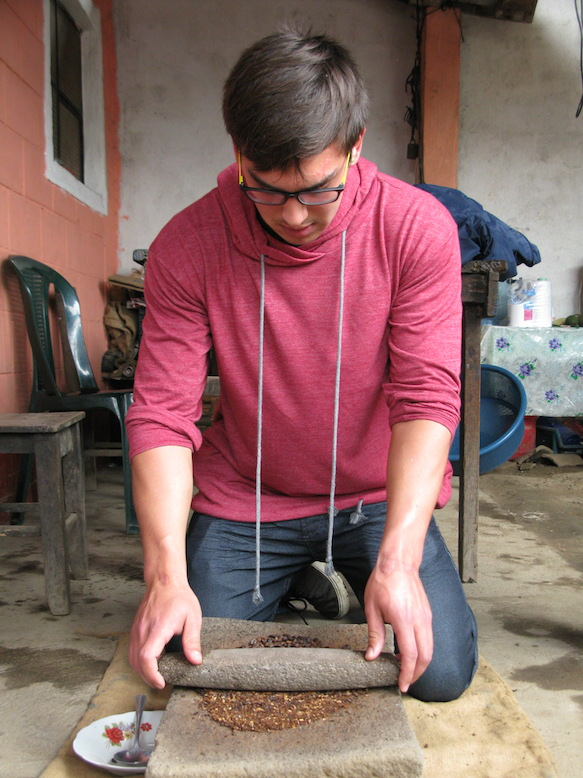 Another participant grinds the freshly roasted beans.