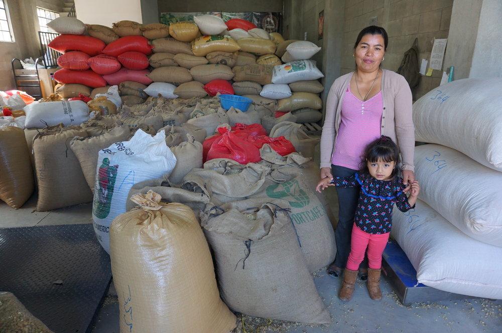 Blandi with her youngest daughter Kimberli, among UPC's coffee sacks.
