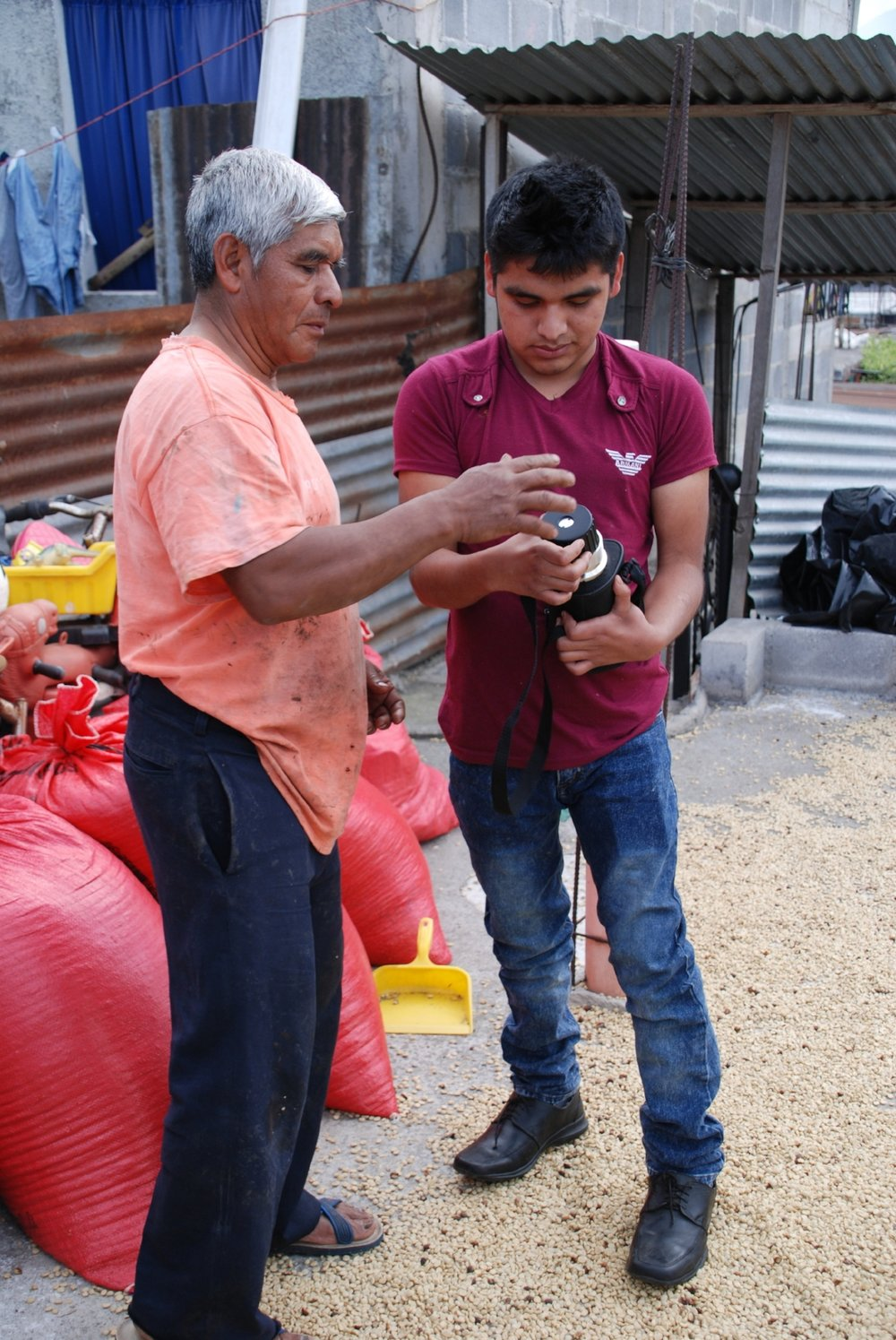 Alvaro, a law student, controlling coffee humidity with his father Miguel