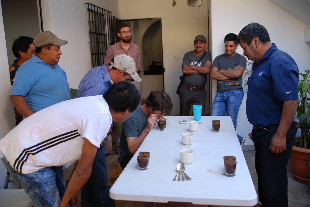 Farmers cupping their microlots with the judges of the competition
